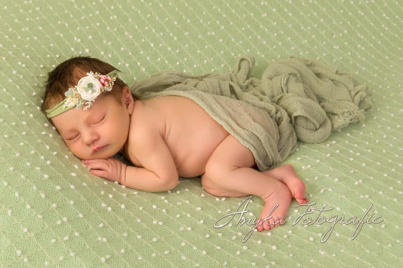 Liggend op haar zij tijdens een newborn shoot 33844