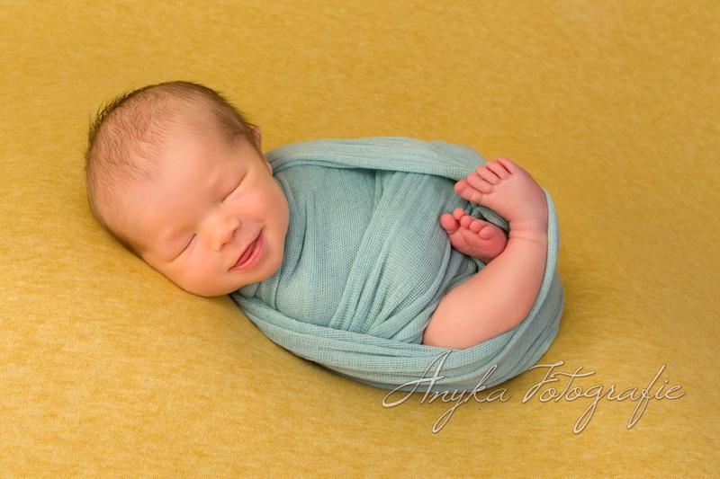 wrapped newborn baby op beanbag tijdens zijn baby fotoshoot 35606
